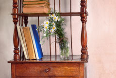 Shelves retro. Old retro shelves with old books and a bouquet of meadow flowers Royalty Free Stock Photo