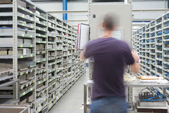 Shelves with spare parts and technician in motion. Metal shelves with spare parts and technician in motion, person not recognizable Stock Images