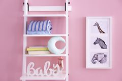 Shelves with toys and pictures of animals on wall. In baby room Stock Image