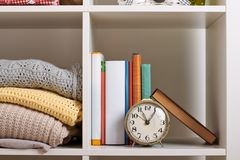 Shelves with various things in the room - books, watches, knitted blankets stock photography