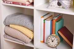 Shelves with various things in the room - books, watches, knitted blankets stock photo