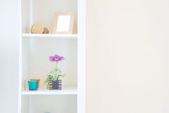 Shelves on the white wall. With mirror and flower royalty free stock photography