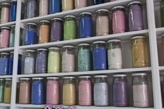 Shelving with glass jars of colorful pigments. Shelving filled with rows of glass jars of colorful pigments in a apothecary or pharmacy in Marrakech, Morocco Royalty Free Stock Photography