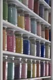 Shelving with glass jars of colorful pigments Stock Photos