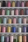 Shelving with glass jars of colorful pigments Royalty Free Stock Photo
