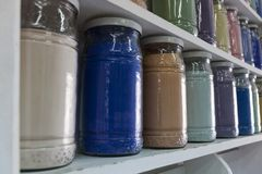 Shelving with glass jars of colorful pigments Stock Images