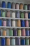 Shelving with glass jars of colorful pigments Stock Photography