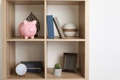 Shelving unit with decorative interior elements piggy bank near white wall. Shelving unit with decorative interior elements and piggy bank near white wall royalty free stock photos