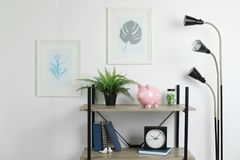 Shelving unit with decorative interior elements. And piggy bank near white wall royalty free stock photo