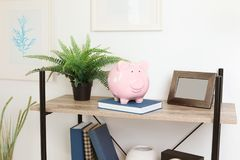 Shelving unit with decorative interior elements. And piggy bank near white wall royalty free stock images