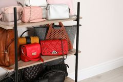 Shelving unit with stylish purses near white wall, space for text. Element of dressing room. Interior royalty free stock photo