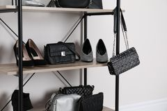 Shelving unit with stylish shoes and purses near white wall stock images