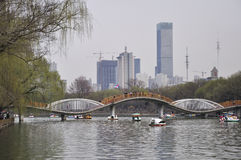 Shenyang south lake park. Spring has come, people go boating in the lake, stone bridge and modern architecture in the distance royalty free stock image