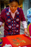 SHENZEN, ΚΊΝΑ - 29 ΙΑΝΟΥΑΡΊΟΥ 2017: Ζωγραφική ατόμων στο κόκκινο διακοσμητικό έμβλημα με τις χρυσές επιστολές, που προετοιμάζοντα Στοκ εικόνες με δικαίωμα ελεύθερης χρήσης