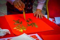 SHENZEN, ΚΊΝΑ - 29 ΙΑΝΟΥΑΡΊΟΥ 2017: Ζωγραφική ατόμων στο κόκκινο διακοσμητικό έμβλημα με τις χρυσές επιστολές, που προετοιμάζοντα Στοκ Φωτογραφίες