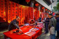 SHENZEN, ΚΊΝΑ - 29 ΙΑΝΟΥΑΡΊΟΥ 2017: Ζωγραφική ατόμων στο κόκκινο διακοσμητικό έμβλημα με τις μαύρες επιστολές, που προετοιμάζοντα Στοκ Εικόνες