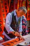 SHENZEN, CHINA - 29 DE ENERO DE 2017: Hombre chino que pinta las letras negras en bandera roja, varias banderas que cuelgan adent Imágenes de archivo libres de regalías