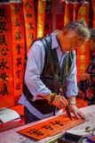 SHENZEN, CHINA - 29 DE ENERO DE 2017: Hombre chino que pinta las letras negras en bandera roja, varias banderas que cuelgan adent Foto de archivo