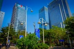 SHENZEN, CHINA - 29 DE ENERO DE 2017: Las calles y los sorroundings del centro urbano, mezcla hermosa de árboles verdes combinaro Foto de archivo libre de regalías