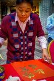 SHENZEN, CHINA - 29 DE ENERO DE 2017: Sirva la pintura en bandera decorativa roja con las letras de oro, preparándose para nuevo  Imágenes de archivo libres de regalías