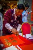 SHENZEN, CHINA - 29 DE ENERO DE 2017: Sirva la pintura en bandera decorativa roja con las letras de oro, preparándose para nuevo  Fotos de archivo