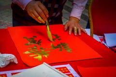 SHENZEN, CHINA - 29 DE ENERO DE 2017: Sirva la pintura en bandera decorativa roja con las letras de oro, preparándose para nuevo  Imagen de archivo