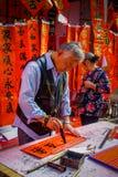 SHENZEN, CHINA - 29 DE ENERO DE 2017: Sirva la pintura en bandera decorativa roja con las letras negras, preparándose para nuevo  Imagen de archivo