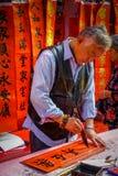 SHENZEN, CHINA - 29. JANUAR 2017: Chinesische Mannmalereigotische schriften auf roter Fahne, einige Fahnen, die herein hängen Stockfoto