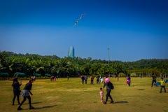 SHENZEN, CHINA - 29. JANUAR 2017: Innerer Lian Hua Shan-Park, großes Erholungsgebiet, Leute, die auf dem Grasspielen laufen Stockfotografie