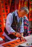 SHENZEN, CHINA - 29 JANUARI, 2017: Chinese mens die zwarte brieven op rode banner schilderen, verscheidene banners die binnen han Royalty-vrije Stock Afbeeldingen