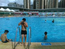 Shenzhen, Κίνα: ` S ηλιόλουστο, αυτό ` s βροχερό, άνδρες και γυναίκες στην πισίνα είτε κολυμπά είτε παίρνει το καταφύγιο από τη β στοκ εικόνα με δικαίωμα ελεύθερης χρήσης