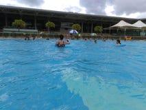Shenzhen, Κίνα: ` S ηλιόλουστο, αυτό ` s βροχερό, άνδρες και γυναίκες στην πισίνα είτε κολυμπά είτε παίρνει το καταφύγιο από τη β στοκ εικόνες με δικαίωμα ελεύθερης χρήσης
