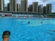 Shenzhen, Κίνα: ` S ηλιόλουστο, αυτό ` s βροχερό, άνδρες και γυναίκες στην πισίνα είτε κολυμπά είτε παίρνει το καταφύγιο από τη β στοκ φωτογραφίες με δικαίωμα ελεύθερης χρήσης