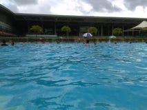 Shenzhen, Κίνα: ` S ηλιόλουστο, αυτό ` s βροχερό, άνδρες και γυναίκες στην πισίνα είτε κολυμπά είτε παίρνει το καταφύγιο από τη β στοκ φωτογραφία με δικαίωμα ελεύθερης χρήσης