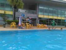 Shenzhen, Κίνα: ` S ηλιόλουστο, αυτό ` s βροχερό, άνδρες και γυναίκες στην πισίνα είτε κολυμπά είτε παίρνει το καταφύγιο από τη β στοκ φωτογραφία