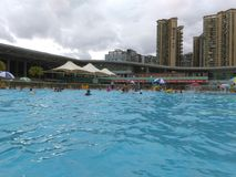 Shenzhen, Κίνα: ` S ηλιόλουστο, αυτό ` s βροχερό, άνδρες και γυναίκες στην πισίνα είτε κολυμπά είτε παίρνει το καταφύγιο από τη β στοκ εικόνες