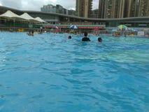 Shenzhen, Κίνα: ` S ηλιόλουστο, αυτό ` s βροχερό, άνδρες και γυναίκες στην πισίνα είτε κολυμπά είτε παίρνει το καταφύγιο από τη β στοκ φωτογραφίες