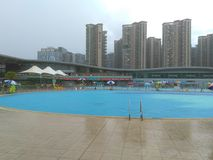Shenzhen, Κίνα: ` S ηλιόλουστο, αυτό ` s βροχερό, άνδρες και γυναίκες στην πισίνα είτε κολυμπά είτε παίρνει το καταφύγιο από τη β στοκ εικόνα