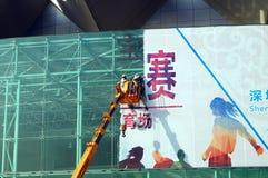 Shenzhen, Κίνα: εργαζόμενοι στην αφαίρεση της διαφήμισης των σημαδιών Στοκ Εικόνες