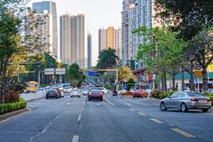 Shenzhen busy city street with moving car, motorcycle, office building, skyscrapers. Chinese downtown Stock Photos