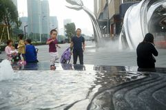 Shenzhen, China: adults and children play around the fountain in the shopping mall Royalty Free Stock Image
