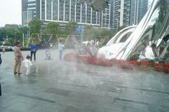 Shenzhen, China: adults and children play around the fountain in the shopping mall. In the morning, Yi Fang Cheng shopping mall fountain pool, adults and Royalty Free Stock Image