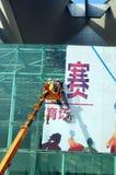 Shenzhen, China: arbeiders in de verwijdering van de reclame van tekens Stock Foto's