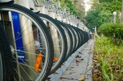 Shenzhen, China: as fileiras de bicicletas compartilhadas estacionaram no passeio Foto de Stock