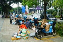 Shenzhen, China: auf Bürgersteigskurierunternehmen verteilen die Angestellten Kundenkurier lizenzfreie stockfotos