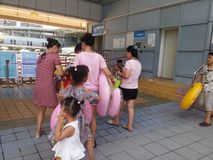 Shenzhen, China: boys and girls go to the swimming pool to buy tickets and go swimming. In hot weather, boys and girls, together with their adults, go to the Royalty Free Stock Images