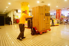Shenzhen, China: Carrefour supermarket employees carry large appliances into the store Royalty Free Stock Photo