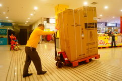 Shenzhen, China: Carrefour supermarket employees carry large appliances into the store Stock Photography