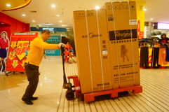 Shenzhen, China: Carrefour supermarket employees carry large appliances into the store Stock Image
