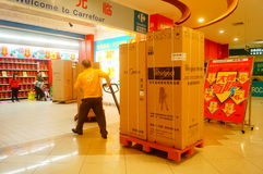 Shenzhen, China: Carrefour supermarket employees carry large appliances into the store Stock Photos
